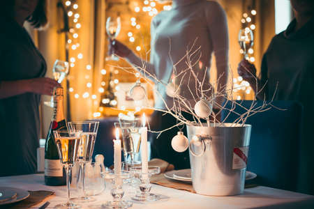 three persons: Christmas or New Year party table with champagne. Three persons stand behind