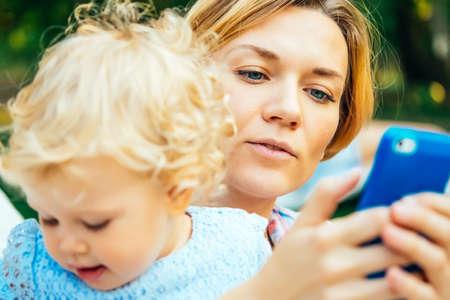 madre y bebe: madre hermosa joven que comprueba los mensajes en su teléfono inteligente durante una caminata al aire libre Foto de archivo