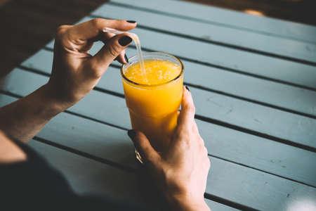 tomando jugo: La mujer está bebiendo zumo de naranja en café de la calle. imagen de tonos