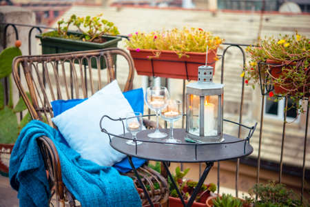 Beautiful terrace or balcony with cozy rattan armchair and candles on small iron table Фото со стока