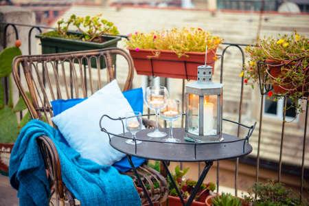 Prachtig terras of balkon met gezellige rattan fauteuil en kaarsen op kleine ijzeren tafel