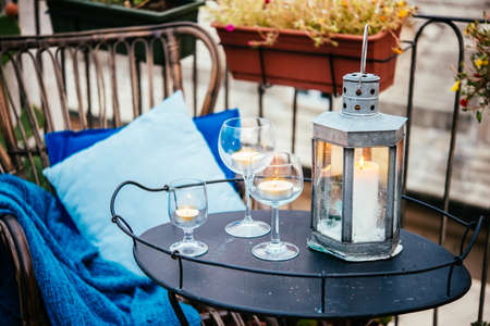 Beautiful terrace or balcony with cozy rattan armchair and candles on small iron table on small iron table