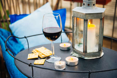 small table: Glass of wine and candles on small iron table on the terrace or balcony
