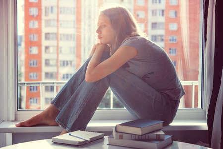 Une adolescente triste assis sur rebord de la fenêtre au lieu de lire des livres sur la table. Image teintée Banque d'images - 50615083