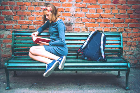 A teenage girl is reading on a bench with brick wall in the background. Toned image Foto de archivo