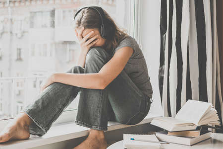 pardon: Une adolescente triste assis sur rebord de la fenêtre écouter de la musique au lieu de lire des livres sur la table. Image teintée