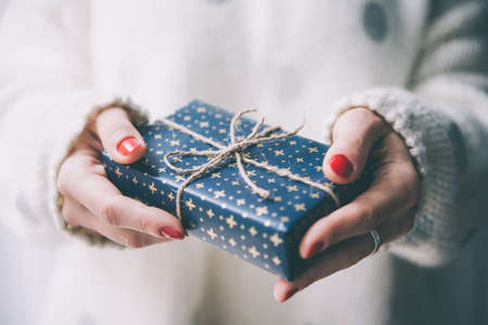 Woman's hands hold christmas or new year decorated gift box. Toned picture