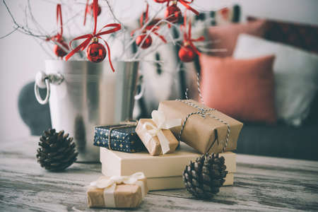 크리스마스 또는 현대 나무 커피 테이블에 새 해 장식. 배경에 베개와 편안한 소파. 거실 인테리어와 휴일 홈 장식 개념입니다. 톤의 그림 스톡 콘텐츠