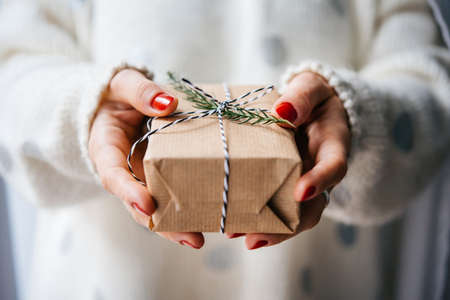 Woman's hands hold christmas or new year decorated gift box