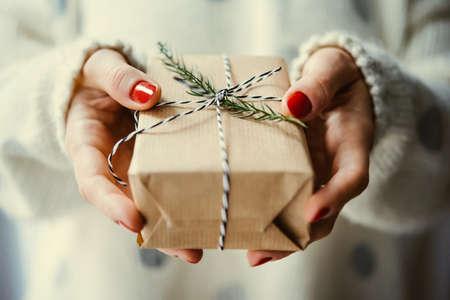 ženské ruce držet vánoční nebo novoroční zdobené dárkové krabičce. tónovaný obraz
