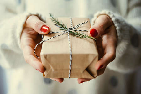 Womans hands hold christmas or new year decorated gift box. Toned picture