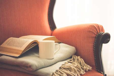 Buch, Tasse und warmen Plaid auf gemütlichen Retro-Sessel. Lesen und Heimtextilien-Konzept. getönten Bild