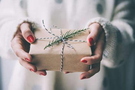 řemeslo: ženské ruce držet vánoční nebo novoroční zdobené dárkové krabičce. tónovaný obraz