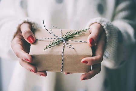 styles: Womans hands hold christmas or new year decorated gift box. Toned picture