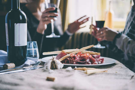 wine: Restaurant or bar table with plate of appetizers and wine. Two people talking on background. Toned picture