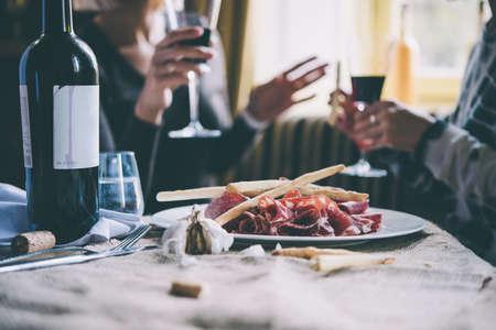 alcool: Restaurant ou table de bar avec plaque d'entrées et de vin. Deux personnes parlant sur fond. image teintée