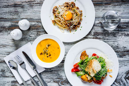 Three plates with lunch dishes on wooden table. Caesar salad, pumpkin soup and pasta carbonara