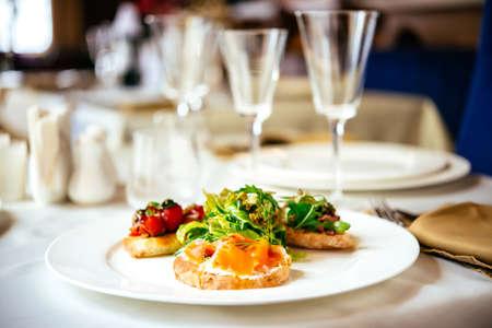 restaurante italiano: Placa de una variedad de bruschetta aperitivo italiano con verduras picadas, el salmón y la carne con pan ciabatta, con guarnición de ensalada de mezcla verde