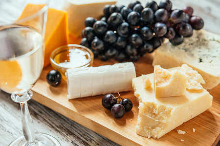 Different types of cheese with grape on wooden board served with the glass of white wine. Toned image