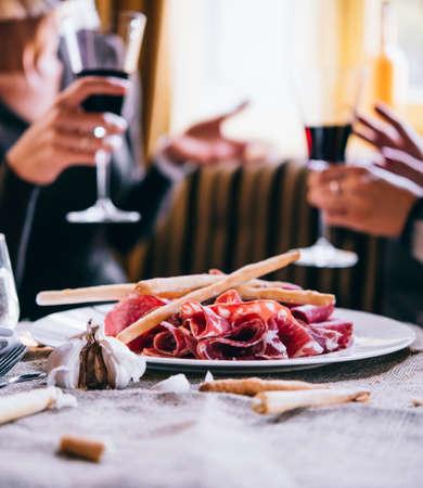 Restaurant oder Bar Tisch mit Platte von Vorspeisen und Wein. Zwei Menschen im Hintergrund im Gespräch Lizenzfreie Bilder