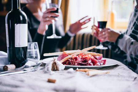 食物: 餐廳或酒吧表開胃菜和酒的盤子。兩個人在談話的背景