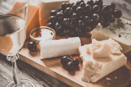 white board: Different types of cheese with grape on wooden board served with the glass of white wine. Toned image
