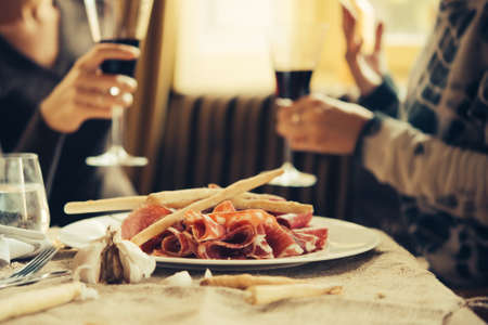 Restaurant or bar table with plate of appetizers and wine. Two people talking on background. Toned picture