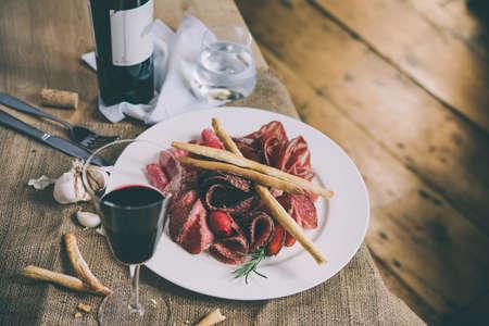 전채 또는 타파스 - 소시지, 고기와 살라미 - 와인과 유리 병 하얀 접시에. 톤 이미지