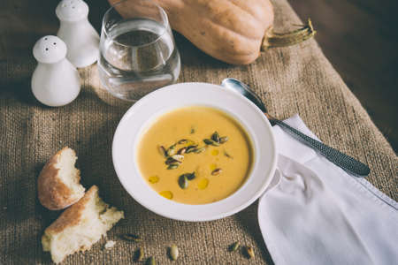 Roasted pumpkin and carrot soup and pumpkin seeds. Toned picture