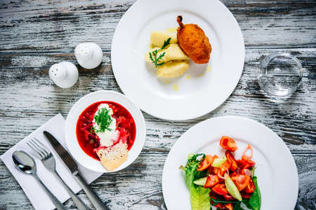 Three plates with lunch dishes on wooden table. Vegetable salad, bosch soup and Chicken Kiev with potato