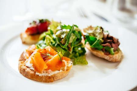 Placa de una variedad de bruschetta aperitivo italiano con verduras picadas, el salmón y la carne con pan ciabatta, con guarnición de ensalada de mezcla verde