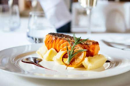 salmone alla griglia con purea di patate e rosmarino lascia sul piatto bianco. messa a fuoco selettiva e superficiale DOF