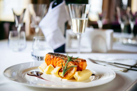 Grilled salmon with potato puree and rosemary leaves on white plate. Selective focus and shallow DOF Stockfoto