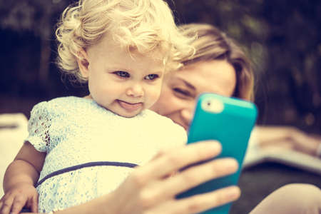 new filter: Young beautiful mother takes selfie with her daughter during a walk outdoors. Toned image