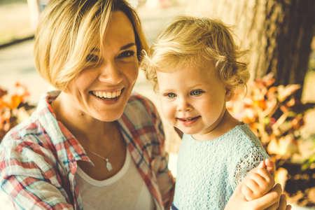 乳幼児: 彼女の小さな娘の若い美しい金髪母親。トーンのイメージ