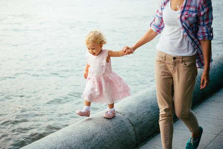 젊은 아름 다운 어머니는 강 근처에 그녀의 딸과 함께 산책 스톡 콘텐츠
