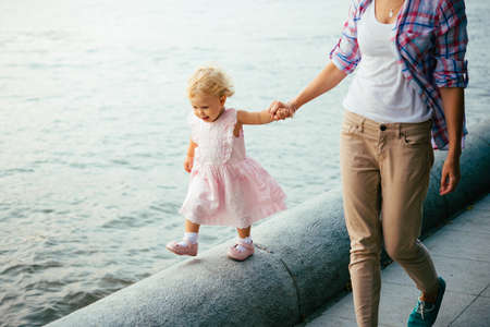 toddler: Young beautiful mother walks with her daughter near the river