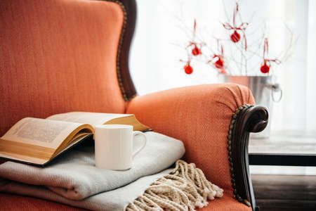 furniture home: Book, cup and warm plaid on cozy retro armchair. Christmas or new year decoration concept