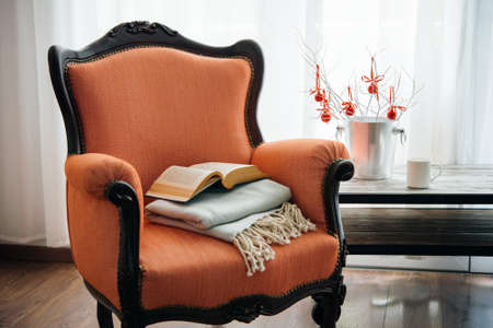 vintage living room: Book, cup and warm plaid on cozy retro armchair. Christmas or new year decoration concept