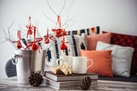 room decoration: Christmas or new year decoration on modern wooden coffee table. Cozy sofa with pillows on a background. Living room interior and holiday home decor concept