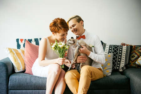 Cute lesbian couple in wedding outfits sitting with their cat. Gay marriage concept. Stock Photo
