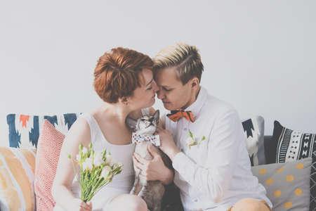 couple de lesbiennes mignon dans des tenues de mariage assis dans le fauteuil. concept de mariage gay. image teintée