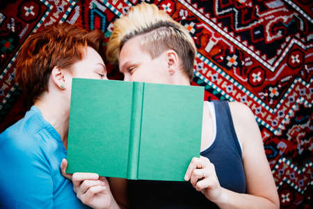 adult sex: Cute lesbian couple read together lying on the carpet. Selective focus on book