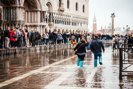 VENICE, ITALY - OCTOBER 14, 2015: Tourists wearing rain boots walk around San Marco square in rainy weather in Venice, Italy. Editorial