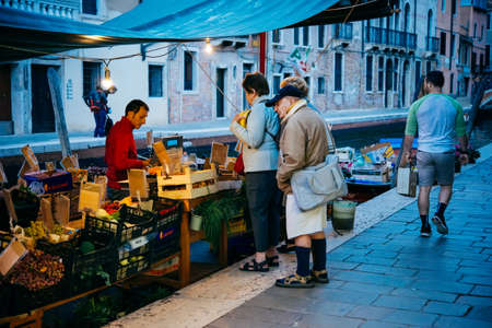 the merchant of venice: VENICE, ITALY - OCTOBER 12, 2015: A small local evening market in one of the streets in Venice, Italy.