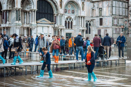 rain boots: VENICE, ITALY - OCTOBER 14, 2015: Tourists wearing rain boots walk around San Marco square in rainy weather in Venice, Italy. Editorial