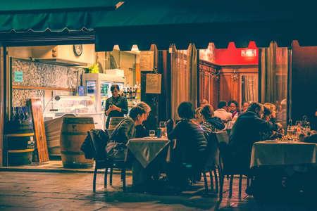 personas comiendo: VENECIA, Italia - 11 de octubre: La gente está sentada en la terraza exterior de un pequeño café en la noche en Venecia, Italia. cuadro entonado