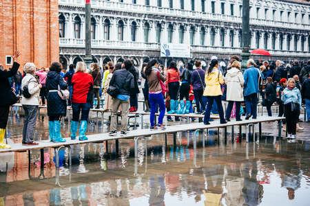 san marco: VENICE, ITALY - OCTOBER 14, 2015: Tourists wearing rain boots walk around San Marco square in rainy weather in Venice, Italy. Editorial