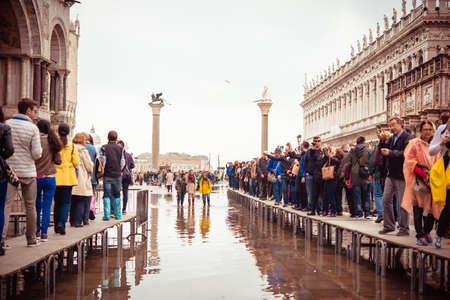 VENICE, ITALY - OCTOBER 14, 2015: Tourists wearing rain boots walk around San Marco square in rainy weather in Venice, Italy.