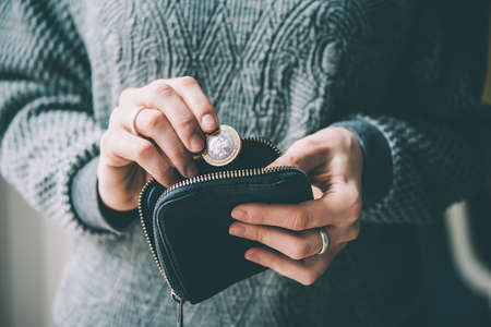 Hände halten britische Pfund-Münze und kleinen Geldbeutel. getönten Bild